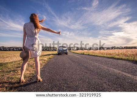 young woman hitch-hiking on a road at the fields - stock photo