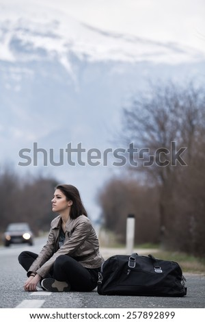 Young woman hitchhiking on countryside road.Traveler woman sitting alone along the road.Pretty young woman tourist hitchhiking.Left alone on the road and lost - stock photo
