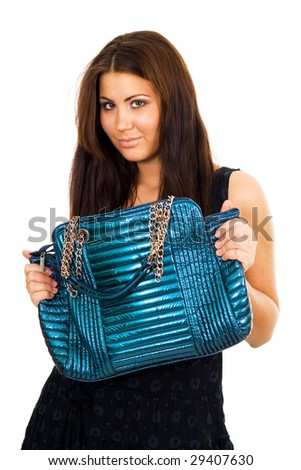 Young woman hoding big blue vivid purse with two hands and looking to camera slightly smiling