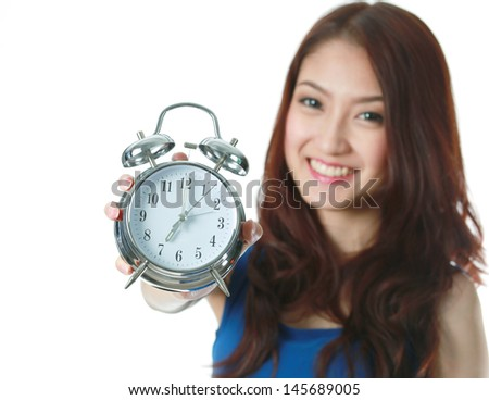 Young woman holdalarm clock at seven o'clock, focus on foreground - stock photo
