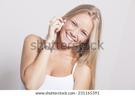 Young Woman hold cell phone smartphone and smiling - stock photo