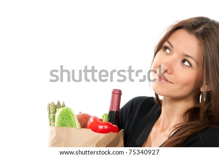 Young woman hold shopping paper bag full of vegetarian groceries, red pepper, salad, bottle of dry wine, mango isolated on white background. Close-up composition - stock photo