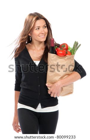 Young woman hold shopping paper bag full of vegetarian groceries, red pepper, salad, bottle of dry wine, asparagus, fresh organic tomatoes isolated on white background. - stock photo