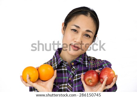 Young woman holding a apple and oranges looking into the camera. Portrait of Asia. Isolated