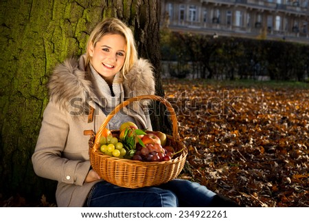 young woman holding a basket full of fruits in a park during autumn