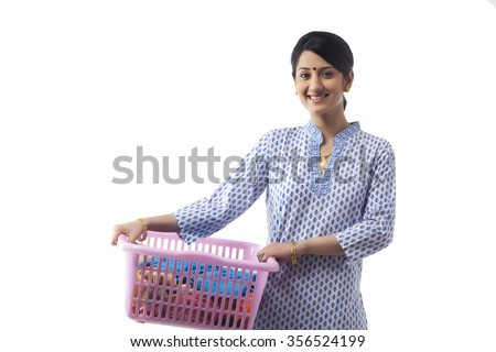 Young woman holding a basket of clothes
