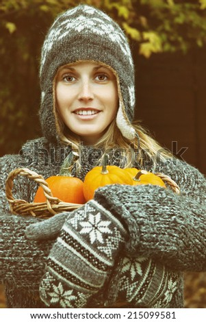 Young woman holding a basket of small pumpkins