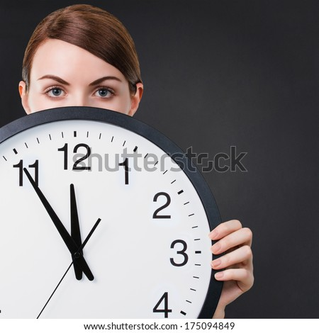Young woman holding a big clock against back chalkboard background with copy space. Time or business concept - stock photo