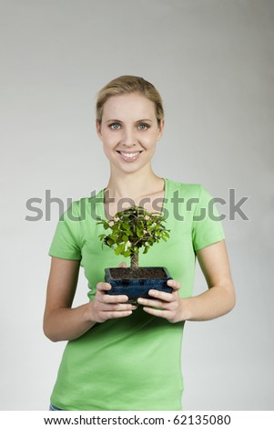 Young woman holding a bonsai tree