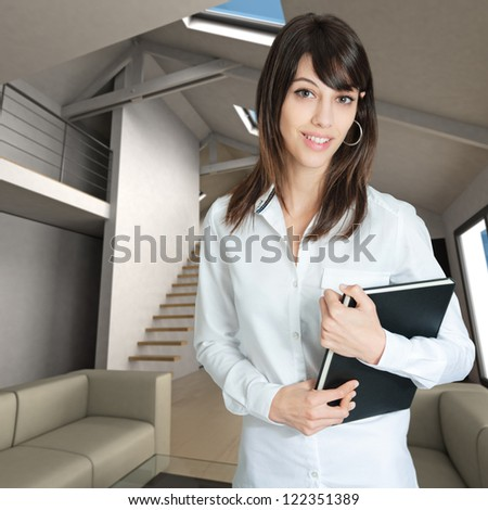 Young woman holding a book standing on a home interior - stock photo