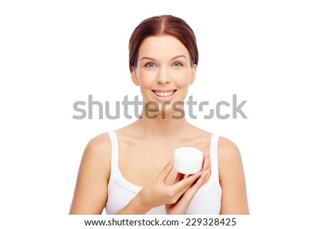 Young woman holding a box with facial or body cream - stock photo
