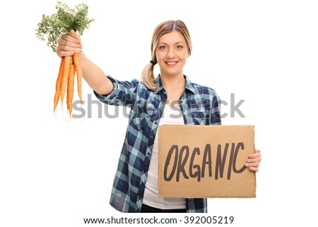 Young woman holding a bunch of carrots and a cardboard sign that says organic isolated on white background - stock photo