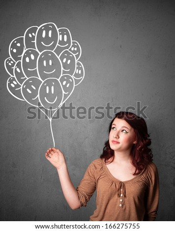 Young woman holding a bunch of smiling balloons - stock photo