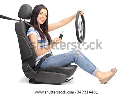 Young woman holding a car key and a steering wheel seated on a car seat isolated on white background - stock photo