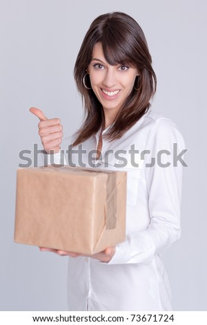 Young woman holding a cardboard box with a happy expression and doing the ok hand sign - stock photo