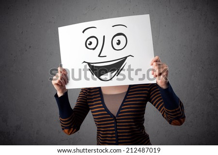 Young woman holding a cardboard with a smiley face on it in front of her head