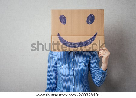 Young woman holding a cardboard with a smiley face on it in front of her head. - stock photo