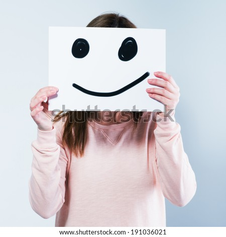 Young woman holding a cardboard with a smiley face on it in front of her head. Photo in color style instagram filters  - stock photo