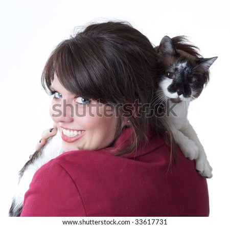 Young woman holding a cat, looking back over her shoulder; isolated on a white background. - stock photo