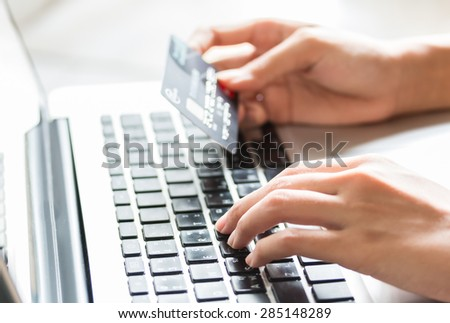 Young woman holding a credit card and typing. On-line shopping on the internet using a laptop - stock photo