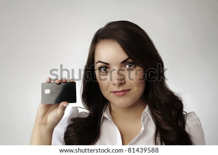 young woman holding a credit cards in her right hand - stock photo