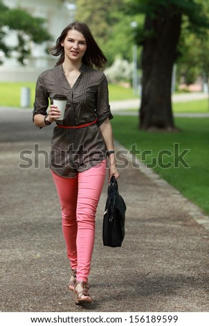 Young woman holding a cup of coffee walking in a hurry outside in a park.