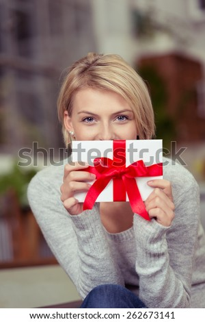 Young woman holding a decorative gift tied with a large red bow in front of her face in a Valentines Day, Christmas or birthday concept for a sweetheart or loved one - stock photo