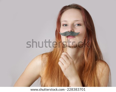 young woman holding a fake moustache on a stick to her face - stock photo