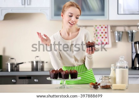 young woman holding a fresh baked cupcake