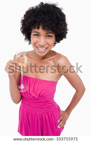 Young woman holding a glass of champagne while putting her hand on her hip - stock photo