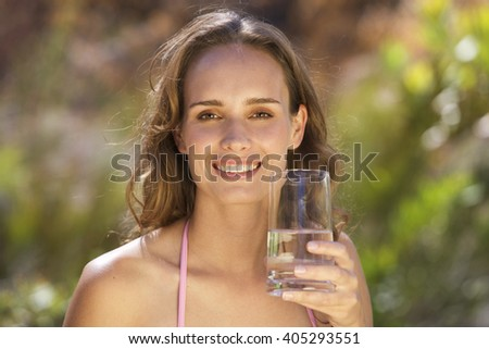 Young woman holding a glass of water, close-up - stock photo