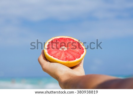 Young woman holding a grapefruit at the beach