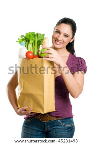 Young woman holding a grocery bag and put in it a fresh apple isolated on white background