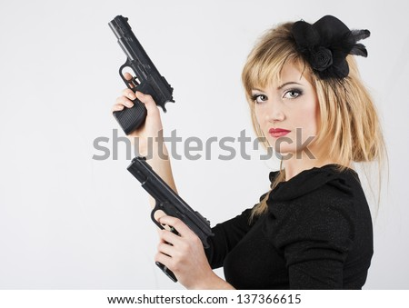 Young woman holding a gun on white background - stock photo