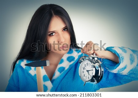 Young Woman Holding a Hammer and an Alarm Clock - Young woman upset with the alarm clock   - stock photo