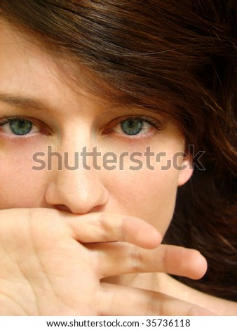 Young woman holding a hand over her mouth - stock photo