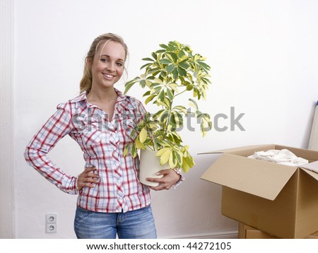 Young woman holding a houseplant with opened moving boxes in a white room. - stock photo