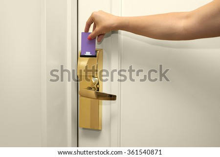 Young woman holding a keycard in front of the electronic sensor of a room door