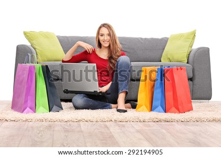 Young woman holding a laptop seated in front of a modern gray sofa with a bunch of shopping bags on the floor around her isolated on white background - stock photo
