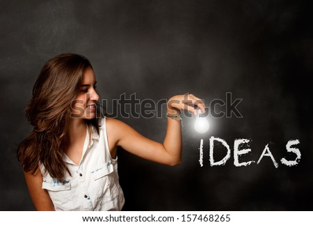 young woman holding a lightbulb composing ideas word - stock photo