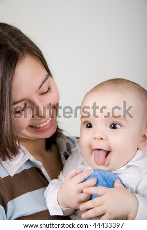 Young woman holding a little baby, baby showing his tongue