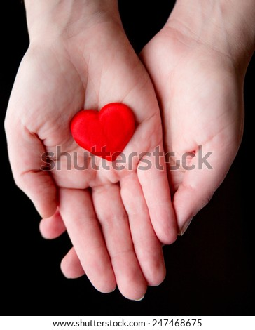 Young woman holding a little red heart in her hands. Health, love, abstract and medical insurance concept - stock photo