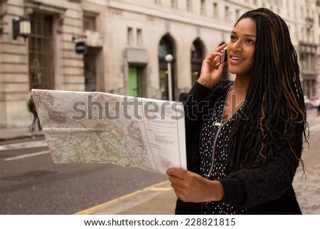 young woman holding a map on the phone.  - stock photo