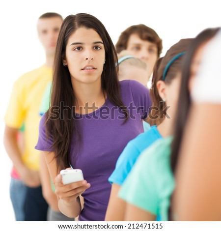 Young woman holding a mobile phone waiting in line. - stock photo