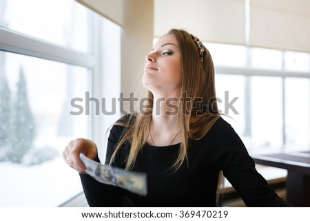Young woman holding a one hundred dollar bill sitting in a cafe waiting for the waiter - stock photo