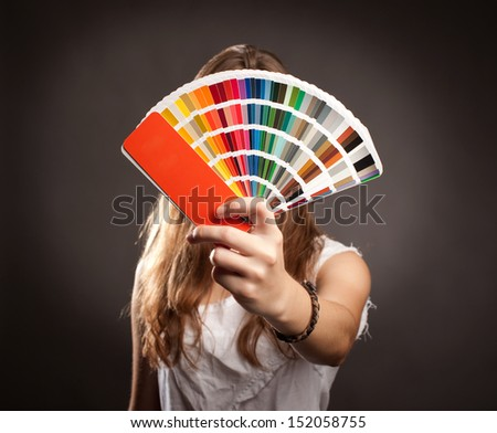 young woman holding a pantone palette - stock photo