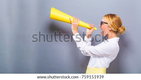 Young woman holding a paper megaphone on a solid background