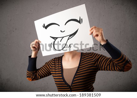 Young woman holding a paper with a cute smiley face on it in front of her head - stock photo