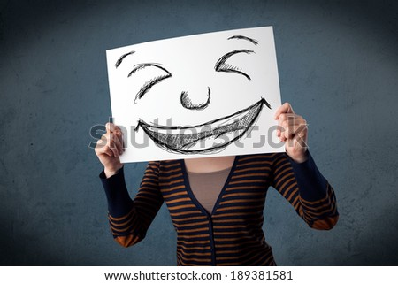 Young woman holding a paper with a drawed smiley face on it in front of her head - stock photo