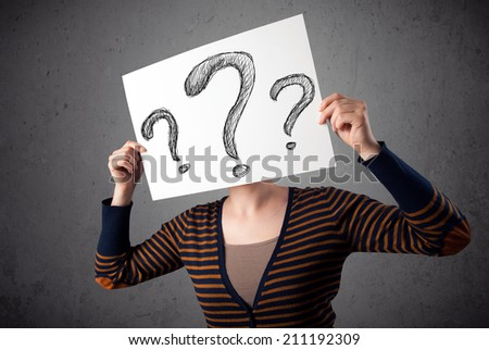 Young woman holding a paper with drawed question marks on it in front of her head - stock photo
